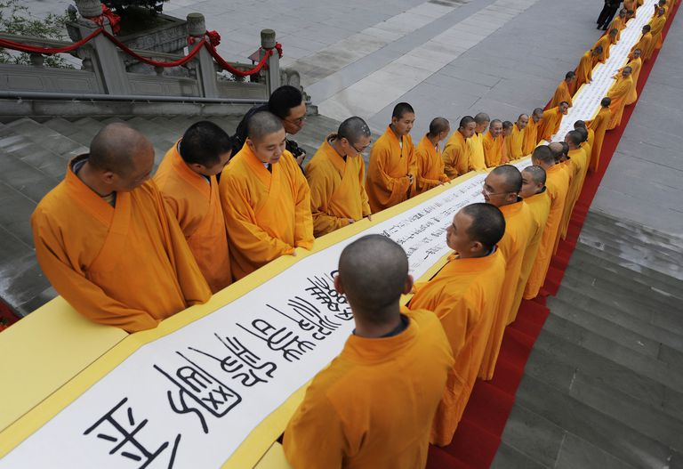 Buddhist monks display a scroll at a temple in Emeishan, Sichuan province