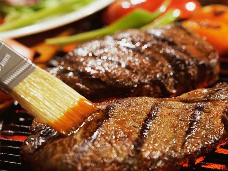 Brushing sauce on grilled steaks