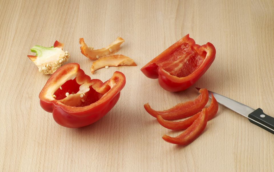 Red bell pepper cored and cut into strips with kitchen knife