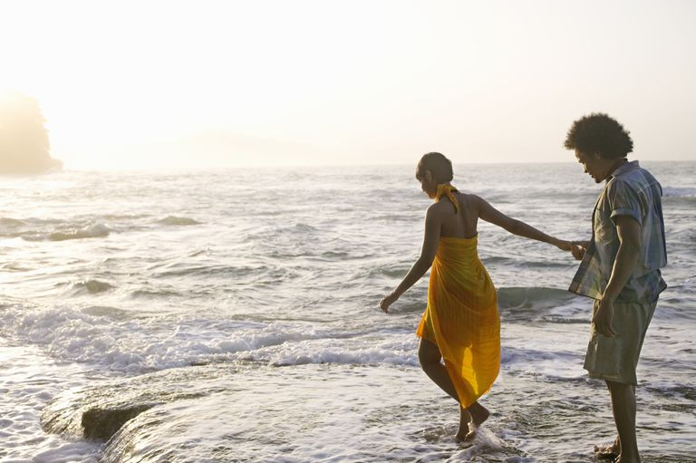 Young couple walking on water's edge on beach