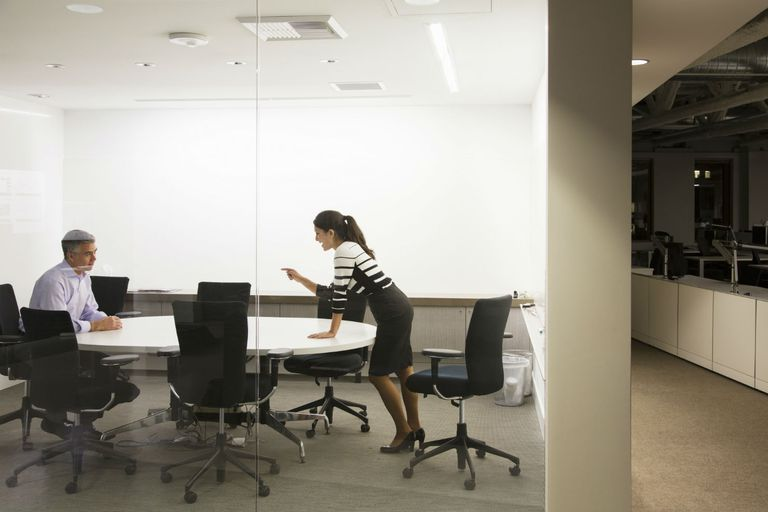 Two business professionals talking in a conference room. Woman standing and pointing at man who is sitting