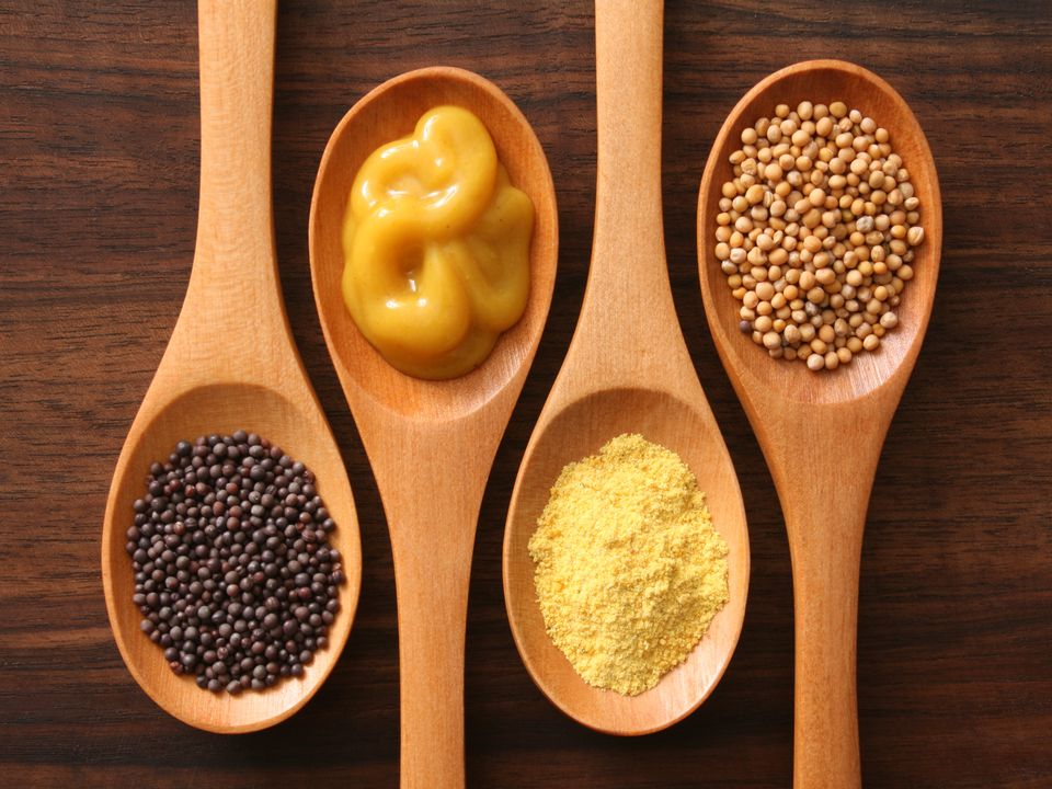Mustard seeds, powder, and prepared mustard on wooden spoons