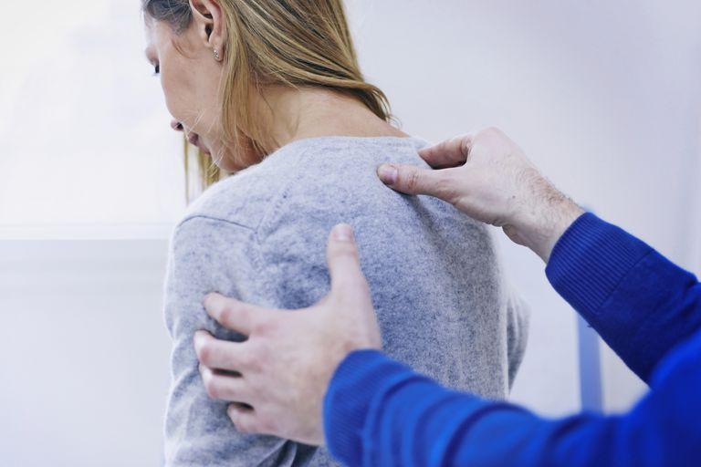 Doctor massaging patient's back
