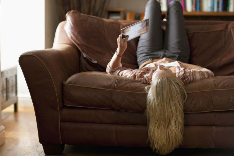 Woman laying upside down on sofa.