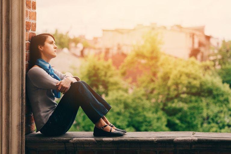 Sad girl sitting outside on a ledge