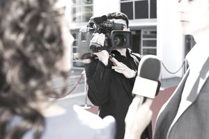 A photo of a TV cameraman shooting an interview with the camera on his shoulder.