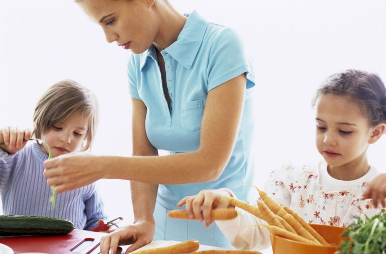 6 year old child development - girl cooking with mother and sibling