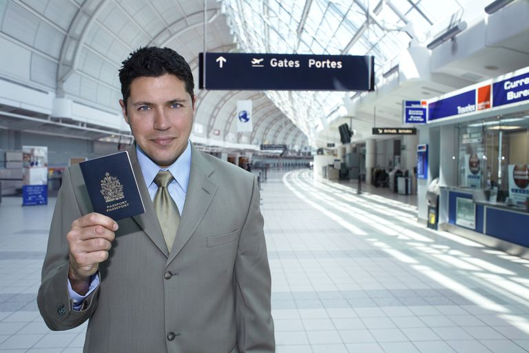 Businessman holding passport at airport, Toronto, Ontario, Canada