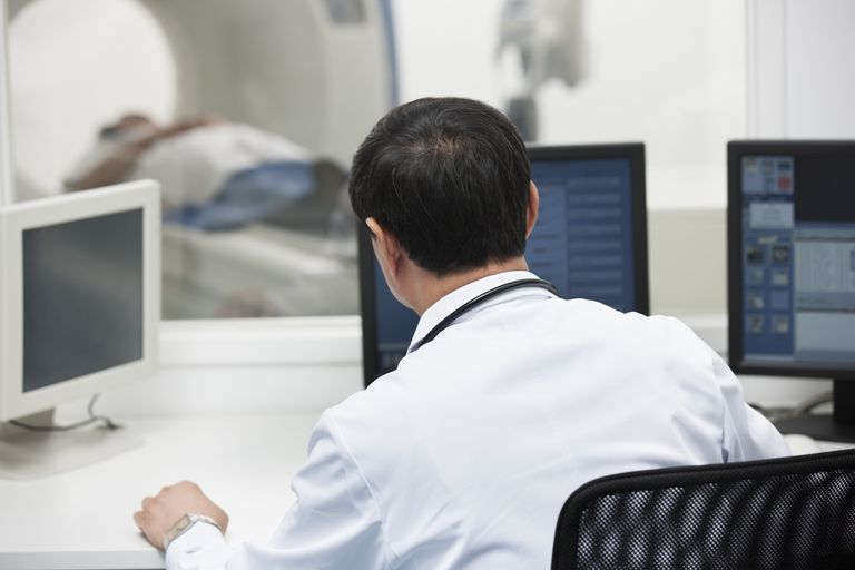 Doctor operating CAT scan machine