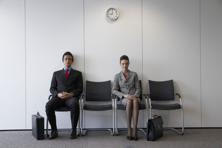 Two people waiting in chairs for interview