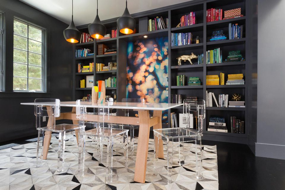 colorful black dining room with ghost chairs