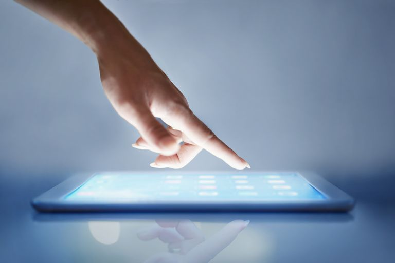 A woman pointing at an iPad.