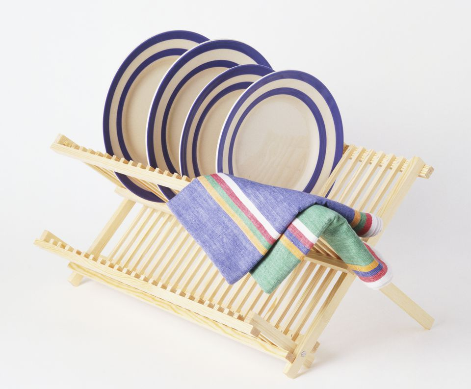 Blue rimmed plates and a two tea towels on a wooden drying rack