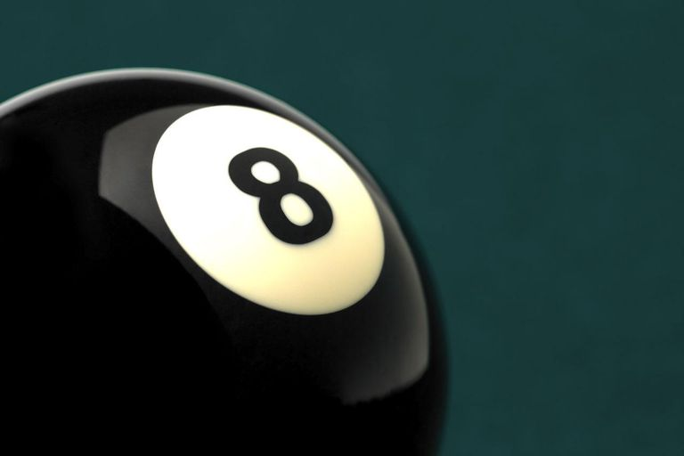 Black ball with the number 8 on it, shot on green pool table. Studio shot, close up, horizontal frame.