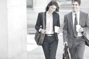Smiling businessman and businesswoman walking with coffee cups