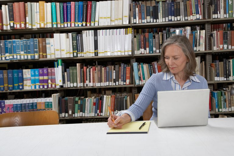 mature woman at library table using laptop and writing notes - Public Librarian Cover Letter