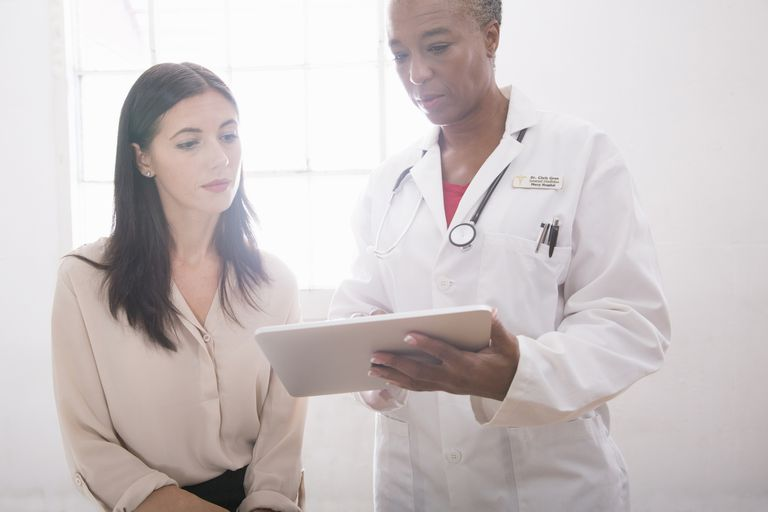 Female doctor using digital tablet in consultation