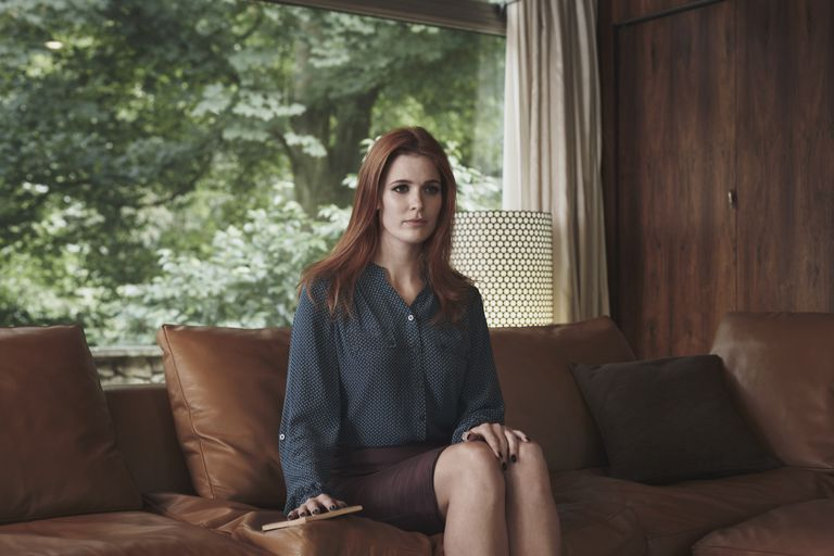 expressionless woman sitting on sofa