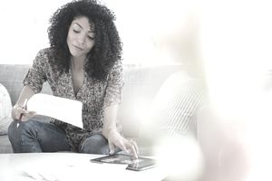 Woman is paying bills using her net pay, what is left after deductions are made by her employer.