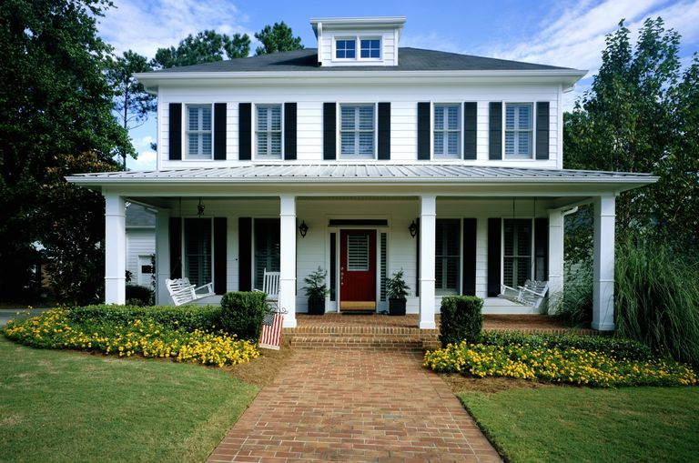 White wooden house, flowers blooming around front porch, brick walkway is an inviting entrance