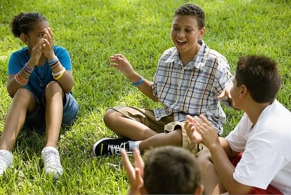 Boy telling stories to his friends while sitting on the grass at a park