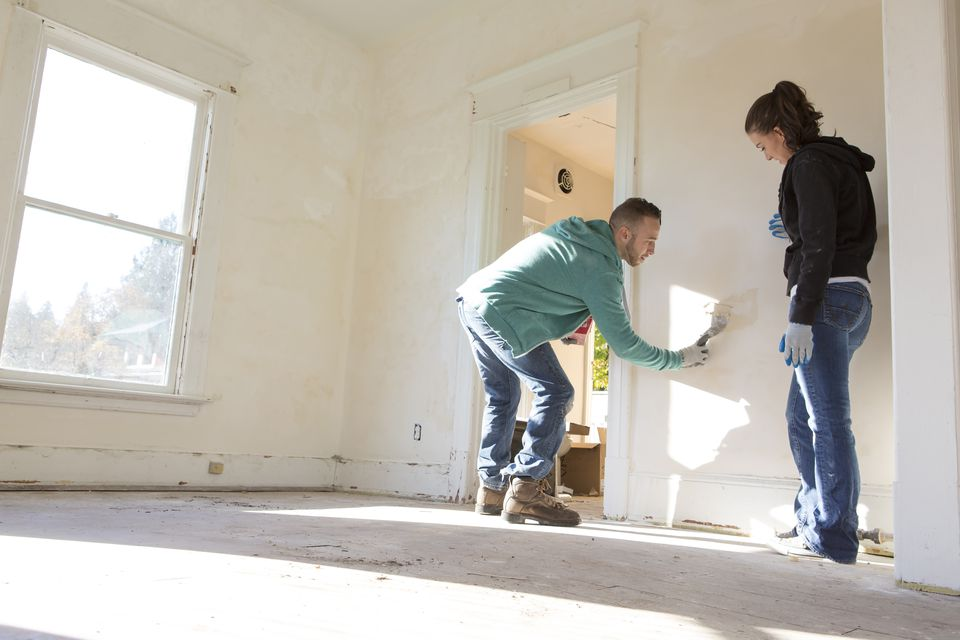 Mixed race couple painting walls of new home