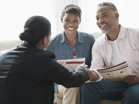 Middle-aged African American couple discussing retirement plans with financial advisor.