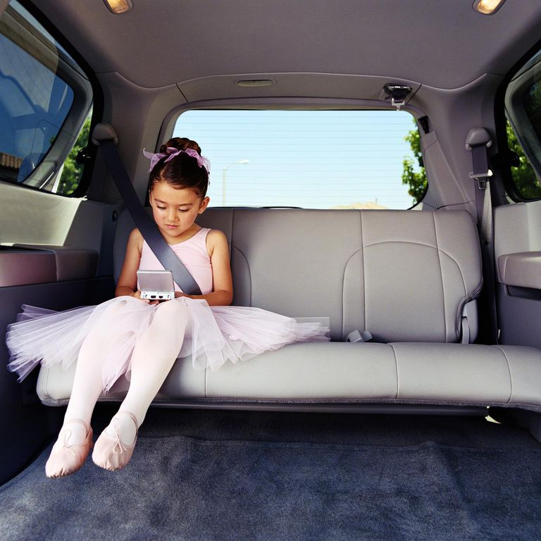 Girl (5-7) in ballet outfit playing video game in backseat of car