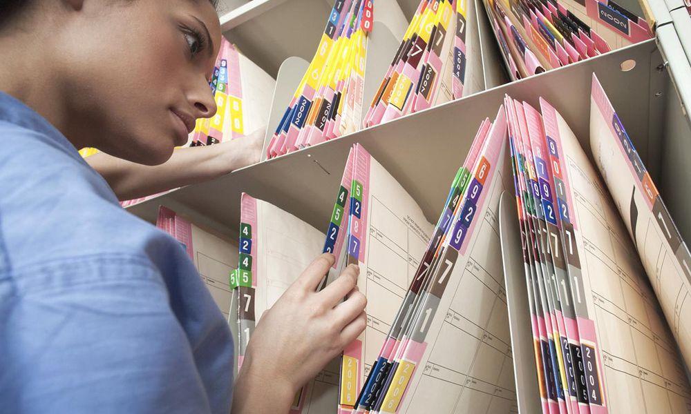 Nurse sorting medical files in hospital