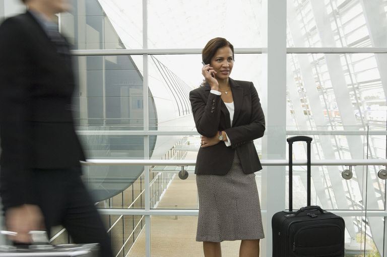 Hispanic business woman in an airport making calls as she travels the world.