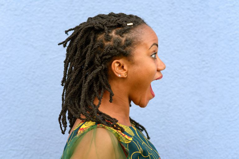 Side View Of Young Woman With Mouth Open Standing Against Wall
