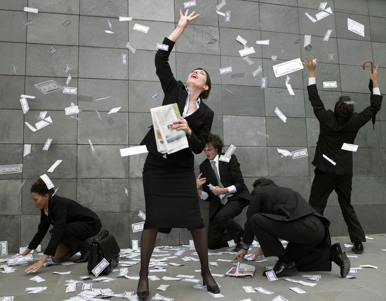 Business people on pavement catching falling money