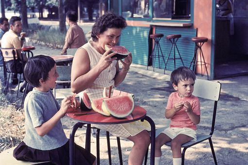 Italian mother and two children eating watermelon outdoors