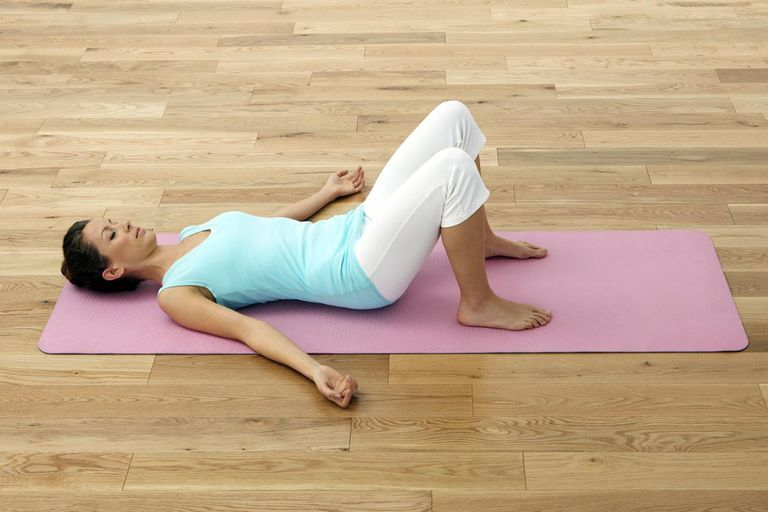 Woman lying on her back on exercise mat, knees bent