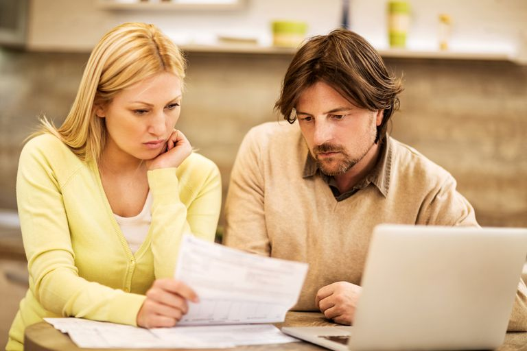 A worried couple reads their credit report