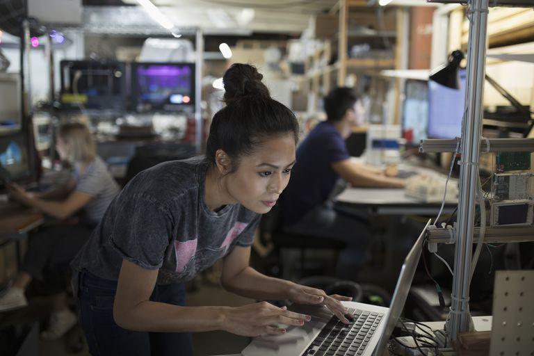 Focused female engineer working at laptop in workshop