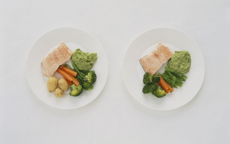 Salmon fillets served with mushy peas and steamed vegetables on plate and new potatoes and steamed vegetables