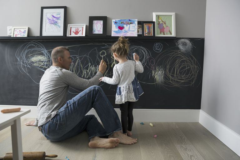 Father and daughter drawing on blackboard wall