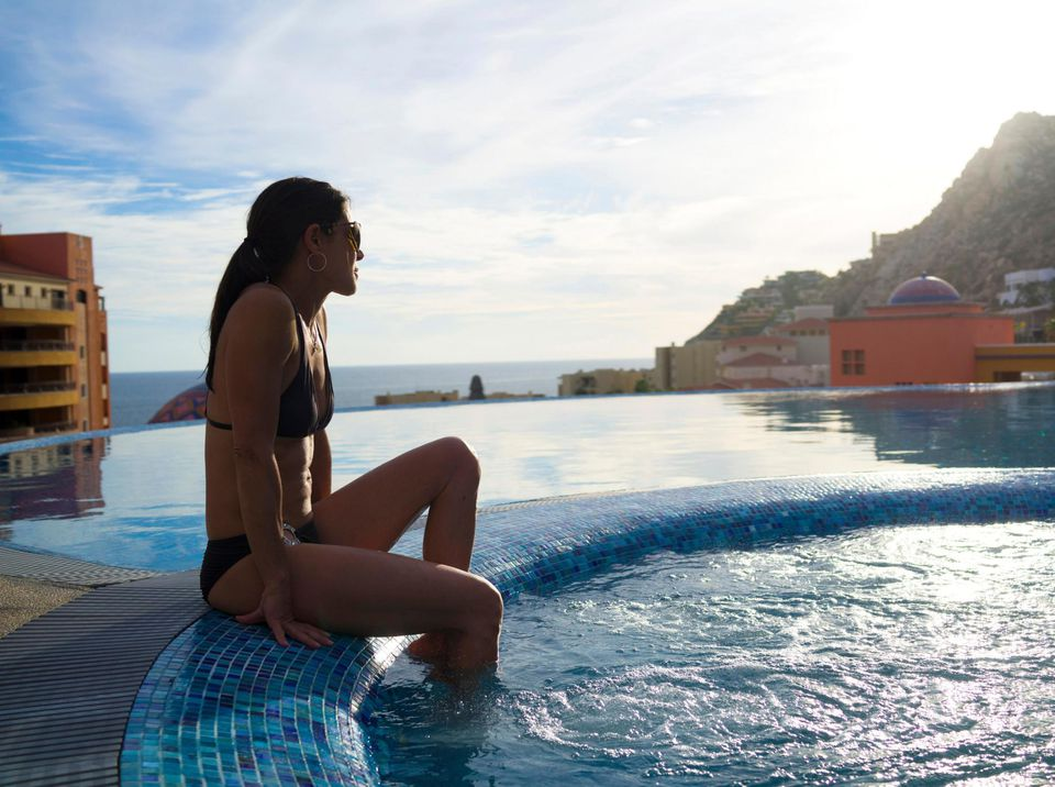 Woman sitting on the edge of a spa at the Playa Grande Ridge Resort in Cabo San Lucas, Mexico