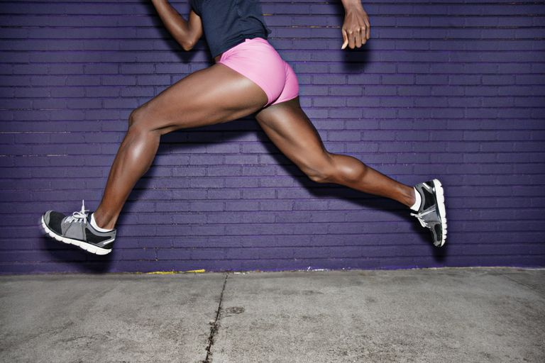 Female athlete running on sidewalk