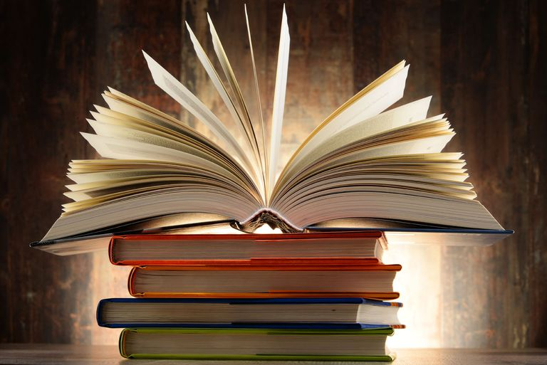 Pile of books with one open