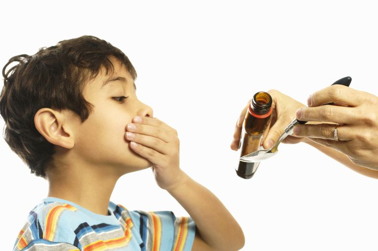 Boy refusing to take cough syrup from his mother