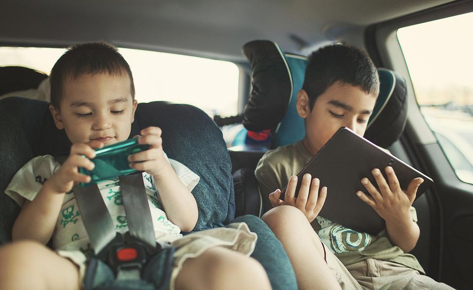 Kids using tablet and gaming device in car