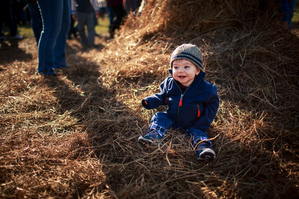 A young boy sits in a stack of hay at a fall festival
