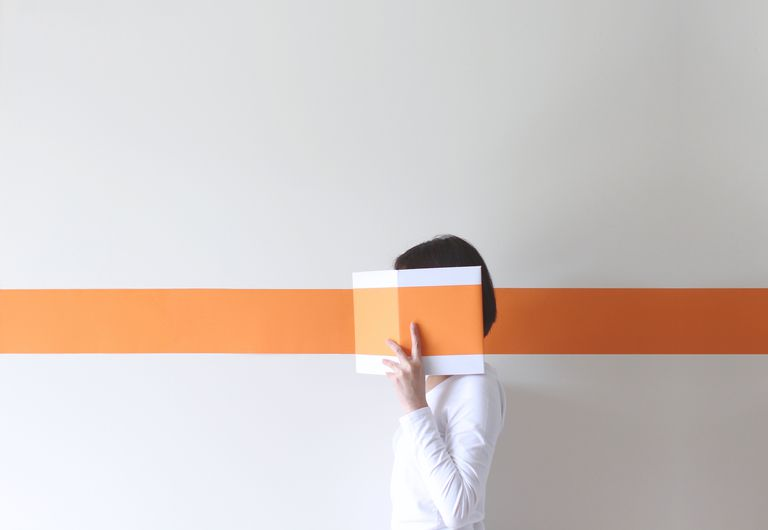 Side view of a mature woman hiding her face behind a book