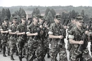 GROUP OF MARINES WEARING CAMOUFLAGE FATIGUES DRILLING MARCHING WITH RIFLES