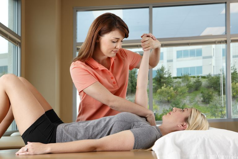 A therapist stretching a patient's shoulder.