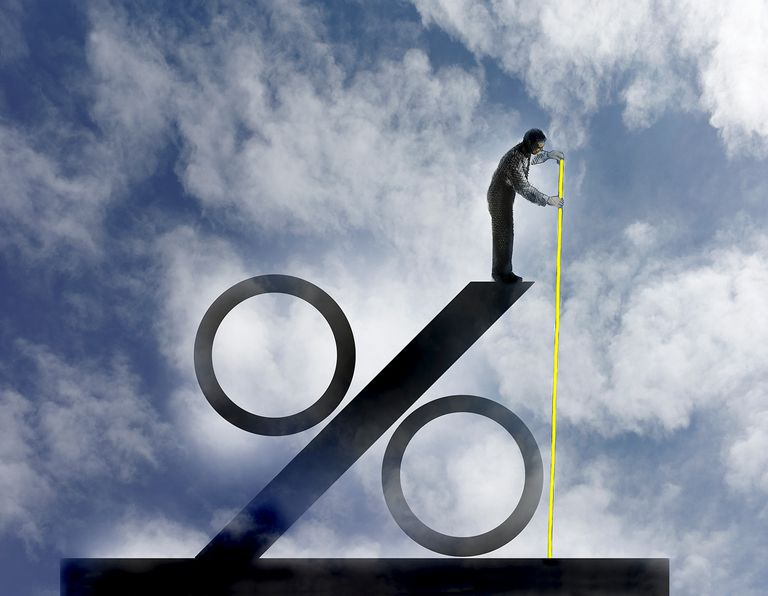 Businessman measuring size of large percentage sign.