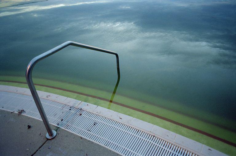 murky swimming pool and hand rail