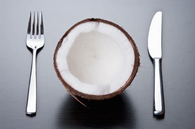 half a coconut with knife and fork